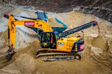 Sand being extracted by machines from a live working quarry in Dorset